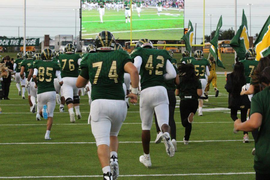 The varsity football players take the field vs. Cy Creek